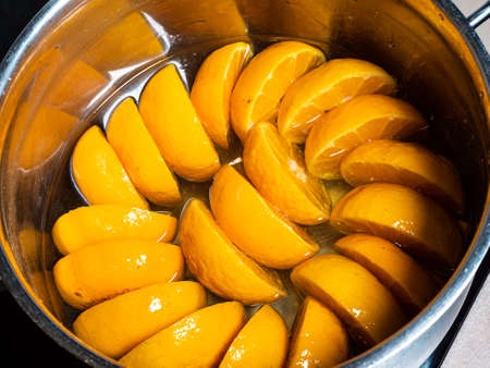 cooking of tangerine jam (varenye) in sugar syrup in stewpot on hob at home kitchen Stock fotó