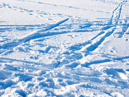 blue surface of snow with ski tracks and footprints lit by setting sun in cold winter twiligh