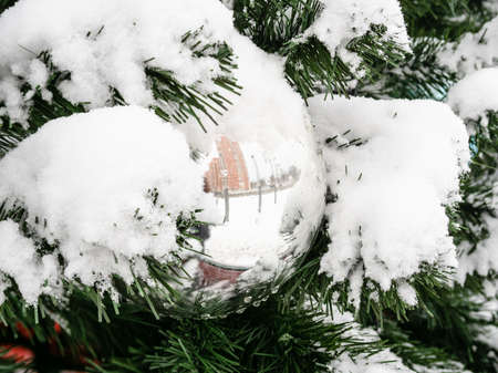 mirrored silver ball on outdoor decorated snow-covered Christmas tree close up on overcast winter day