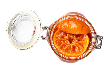 top view of tangerine jam (varenye) in open glass jar cutout on white background