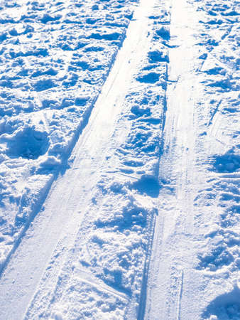 ski track lit by sun close up on snow-covered frozen surface of river on cold in cold sunny winter day