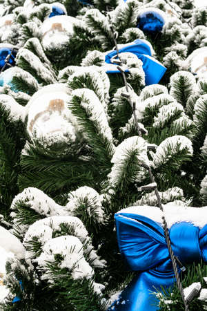 ornaments of outdoor decorated snow-covered Christmas tree close up on overcast winter day