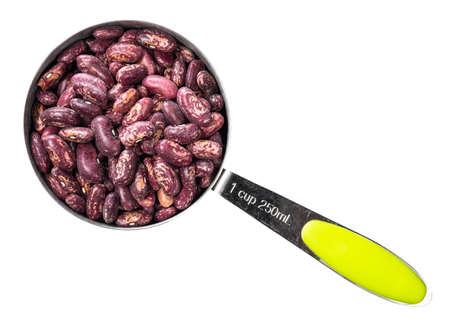 top view of red spotted pinto beans in measuring cup cutout on white background