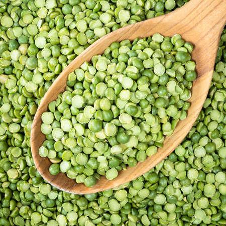 top view of green split peas in wooden spoon closeup