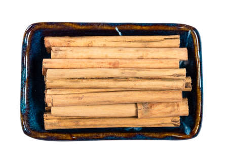 top view of sticks of alba premiumin ceylon cinnamon in ceramic bowl cutout on white background