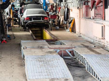 roller brake tester stand inside of old car workshop