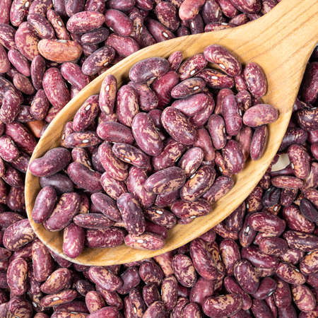 top view of red spotted pinto beans in wooden spoon closeup Foto de archivo
