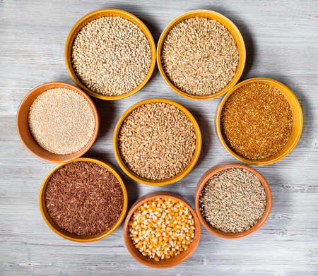 top view of various wholegrain grains (maize, rice, quinoa, millet, rye, wheat, sorghum, oat) in round ceramic bowls on gray wooden table