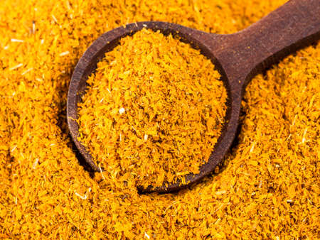 top view of wood spoon on pile of ground Imeretian Saffron (Dried Marigold Flowers) closeup