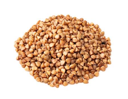 handful of roasted buckwheat grains closeup on white background