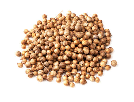 handful of dried coriander seeds closeup on white background