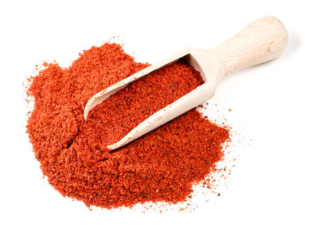 wooden scoop on pile of paprika powder on white background Foto de archivo