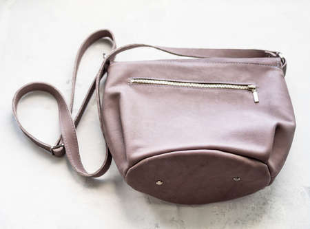 bottom view of handcrafted leather cross body bag with zip fastened pocket on concrete board