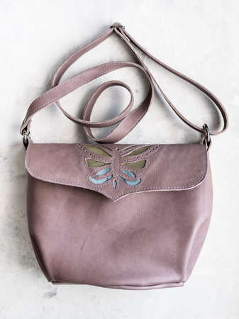 closed handcrafted leather cross body bag with butterfly applique on concrete board
