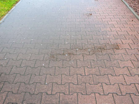 view of path covered by stone tiles in heavy rain on summer day Stock fotó