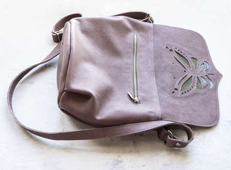 open empty handcrafted leather cross body bag with butterfly applique on concrete board