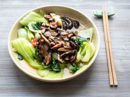 chinese cuisine - Bok choy cabbage with aromatic shiitake mushrooms in ceramic bowl on wooden table Stock fotó