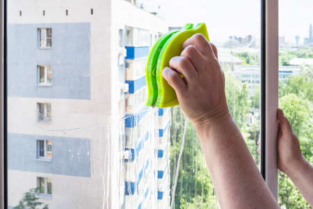 woman cleans home window by double-sided magnetic cleaner in city Stock fotó
