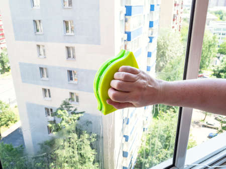 hand with double-sided magnetic cleaner washes home window glass in city Stock fotó