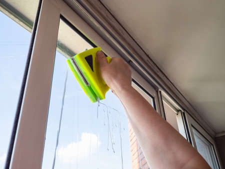 woman washes glazing of loggia with double-sided magnetic cleaner at home Stock fotó