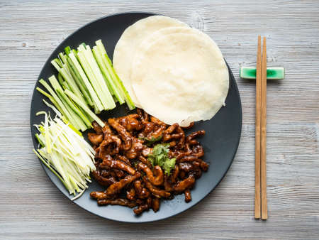 chinese cuisine - top view of pork in peking soy sauce with sliced scallion, cucumber and rice pancakes on black plate on wood table