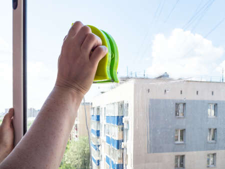 washing home window glass by double-sided magnetic cleaner in city Stock fotó