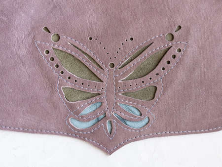 handcrafted butterfly applique on leather cross body bag closeup on concrete board