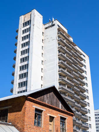 old brick house and modern high-rise apartment building in city with blue sky on sunny summer day