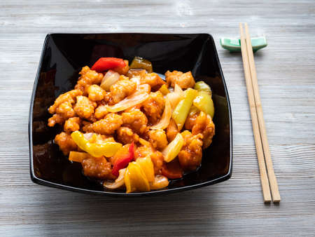 chinese cuisine - Pineapple Fried Chicken in black bowl on wooden table