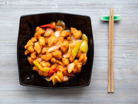 chinese cuisine - top view of Pineapple Fried Chicken in black bowl on wood table