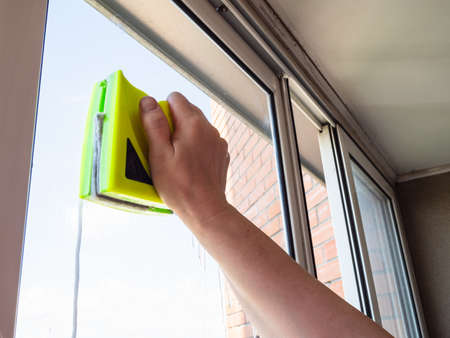 washing glazing of loggia with double-sided magnetic cleaner at home