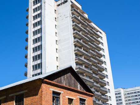 old brick house and modern high-rise apartment building in city on sunny summer day