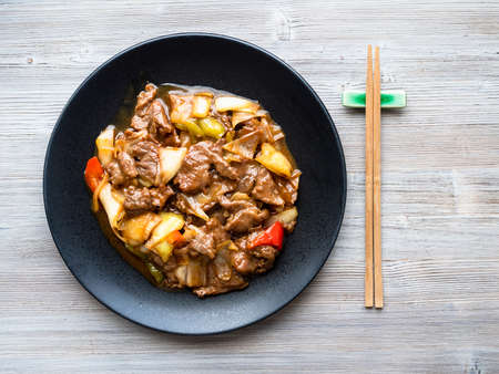 chinese cuisine - top view of stir-fried beef with leeks on black plate on wood table