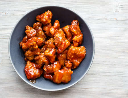 chinese cuisine - top view of sweet and sour pork (guo bao rou) in gray bowl on wooden table