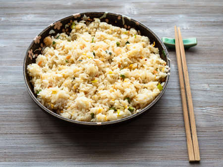 chinese cuisine - yangzhou fried rice in ceramic plate on wooden table