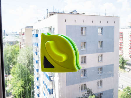 double-sided magnetic cleaner on washing window of urban home Stock fotó