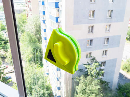 double-sided magnetic cleaner on surface of window of urban home Stock fotó
