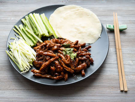 chinese cuisine - pork in peking soy sauce with sliced scallion, cucumber and rice pancakes on black plate on wooden table
