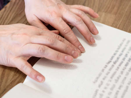 female fingers read book with braille and usual text closeup on wooded table