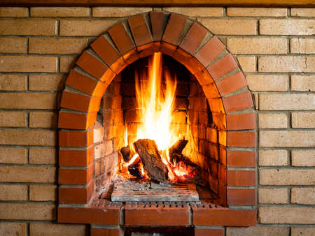 front view of brick fireplace with burning woods in country house