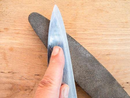 sharpening kitchen knife closeup on whetstone on wooden board