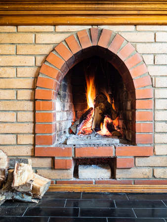 front view of brick fireplace with mantelpiece in country house on cold day