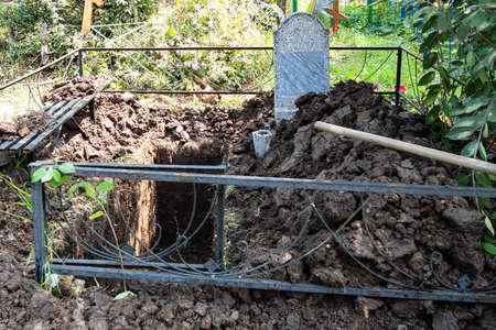freshly dug empty second grave near gravestone in old cemetery Stok Fotoğraf