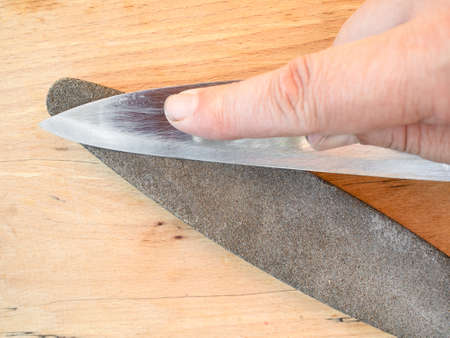 sharpening steel knife close up on whetstone on wooden board Stok Fotoğraf