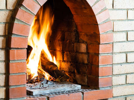 fire in brick fireplace in country house on cold day
