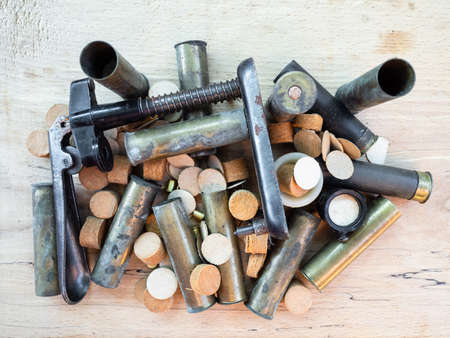 top view of reloading press over cartridge cases, wads, primers on wooden board
