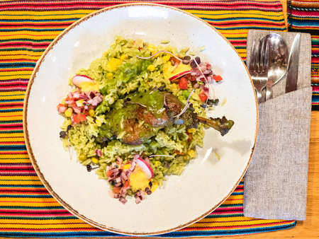 top view of Arroz con Pato - Peruvian dish from duck leg stewed in beer with cilantro, with green rice on plate on table in local restaurant