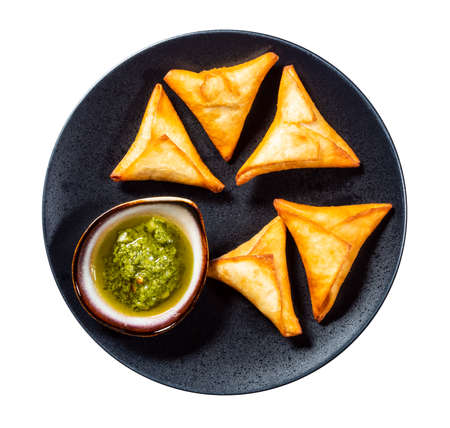 Peruvian Empanadas (fried Turnover filled with meat) with green Chimichurri sauce on plate cutout on white background
