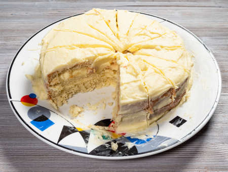 cut home-made sponge cake with butter cream on plate on wooden board