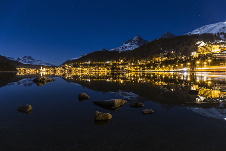Night landscape of St Moritz reflected in the lake in Switzerland.